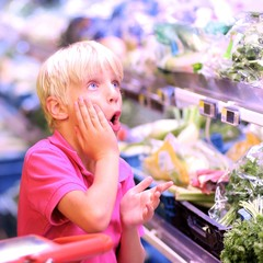 Cute teenager boy at vegetables department in supermarket