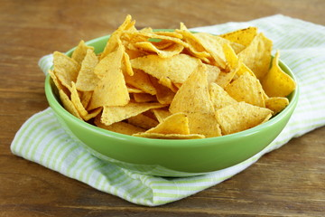 corn chips (nachos) in a green bowl on wooden table