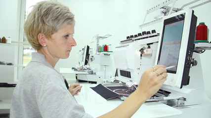 Female engineer working on computerized machine embroidery