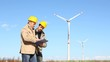 Two Engineers at Work with Wind Turbine on Background