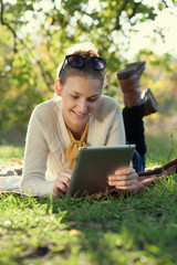 Closeup of happy woman using tablet computer outdoors