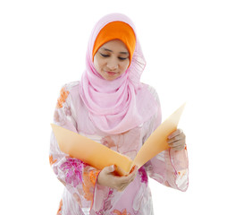 malay muslim girl reading from a folder