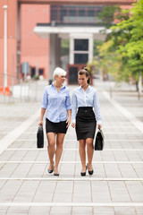 Two businesswoman are walking on the street