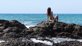 Young attractive woman sitting on the rocks by the sea