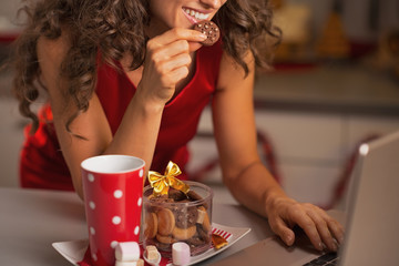 Closeup on happy woman having christmas snacks and usign laptop