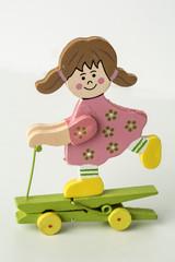 Muñeca de madera sobre patinete