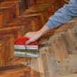 Varnishing of oak parquet floor workers hand brush, renovation