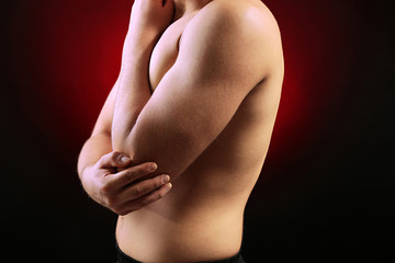 Young man with elbow pain, on red background