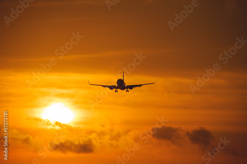 Silhouette of the big plane on a sunset background