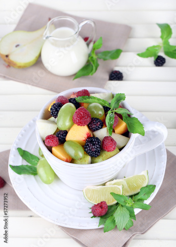 Fruit salad in cup on wooden table
