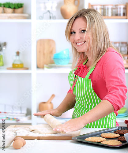 Woman in kitchen during cooking biscuits