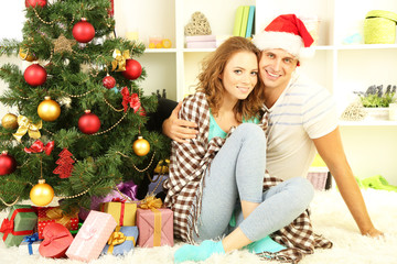Happy young couple near Christmas tree at home