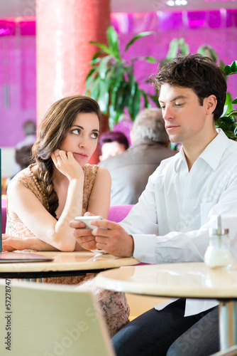 Young couple in cafe not interacting but on phone