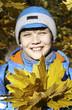 Улыбающийся мальчик с осенними листьями.