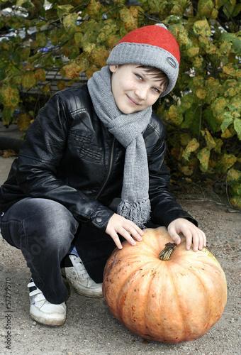 Мальчик с тыквой на садовом участке.Осень