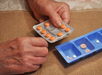 tablets in the hands of an elderly woman