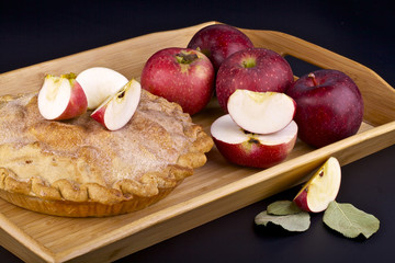 Homemade apple pie in wooden container on background
