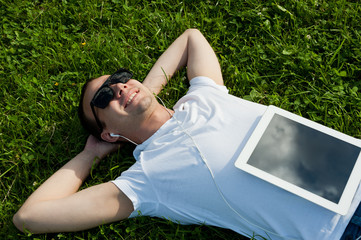 Man lie with tablet on the grass