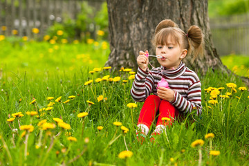 Five-year funny girl blowing soap bubbles in the park