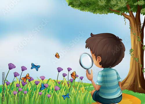 A young boy holding a magnifying lens at the garden in the hillt