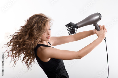 girl dries long hair with hairdryer