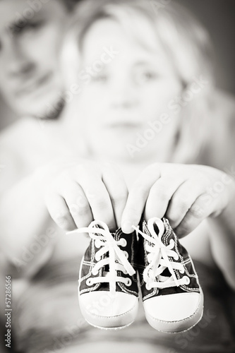 pregnant woman and husband with a child's shoe