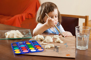 The child learns to paint the dough figurines