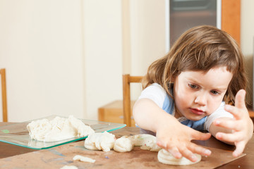 A girl makes dough figurines