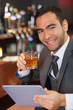 Cheerful businessman working on his tablet while having a whiske