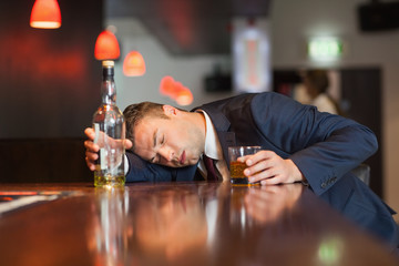Unmoving businessman holding whiskey glass lying on a counter