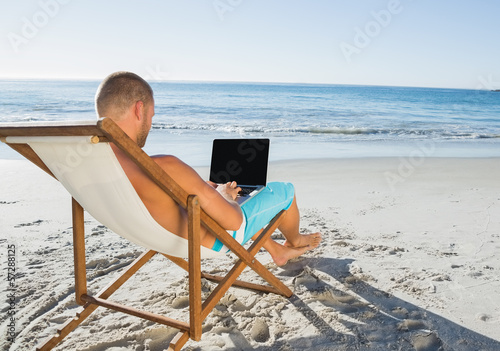 Relaxed handsome man working on his laptop