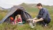 Smiling couple cooking outside on camping trip
