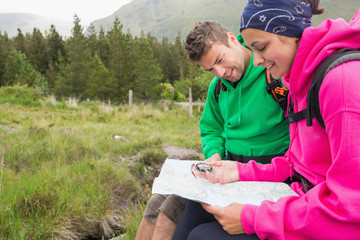 Couple sitting on a rock resting during hike using map and compa