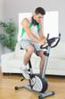 Handsome man training on exercise bike using tablet