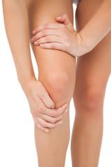 Close up of slim woman touching her injured knee