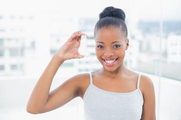 Smiling woman showing asthma inhaler