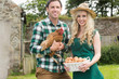 Smiling young couple holding chicken and basket of eggs