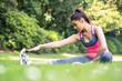 Pretty sporty woman stretching her leg