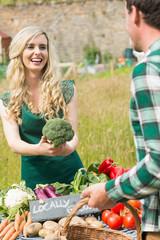 Young female farmer selling organic broccoli