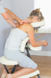 Masseur treating clients shoulder in massage chair