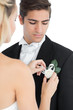 Young bride pinning a flower on her husbands suit