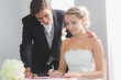 Young blonde bride sitting at table signing wedding register