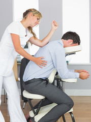Masseuse treating clients back with elbow in massage chair