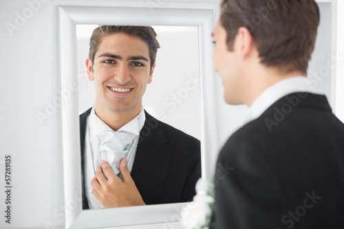 Cheerful young bridegroom standing in front of a mirror