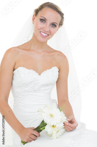 Lovely bride sitting on ground holding a bouquet