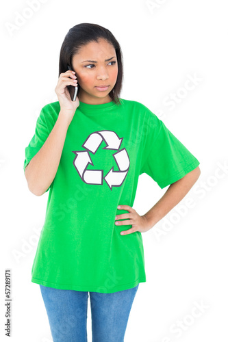 Unsmiling dark haired environmental activist making a phone call