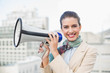 Happy smart brown haired businesswoman holding a megaphone