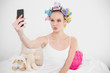 Funny natural brown haired woman in hair curlers taking a pictur