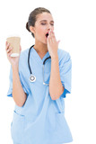 Tired brown haired nurse in blue scrubs yawning and holding a cu