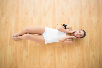 Relaxed natural brown haired woman in white sportswear enjoying